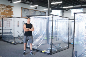 man stands in front of sectioned gym pod